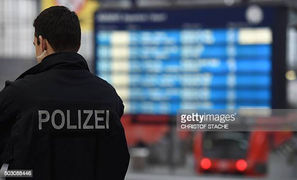 A police officer stands in front of the destination board at the main train station in Munich southern Germany on January 1 2016 German police lifted...
