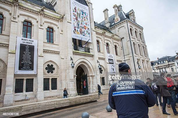 A police officer stands in front of the Hotel de Ville of Angouleme western France after a banner was unveiled on the facade of the building on...
