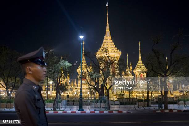 A police officer stands in front of the Royal Crematorium at Sanam Luang ceremonial ground on October 27 2017 in Bangkok Thailand Tens of thousands...