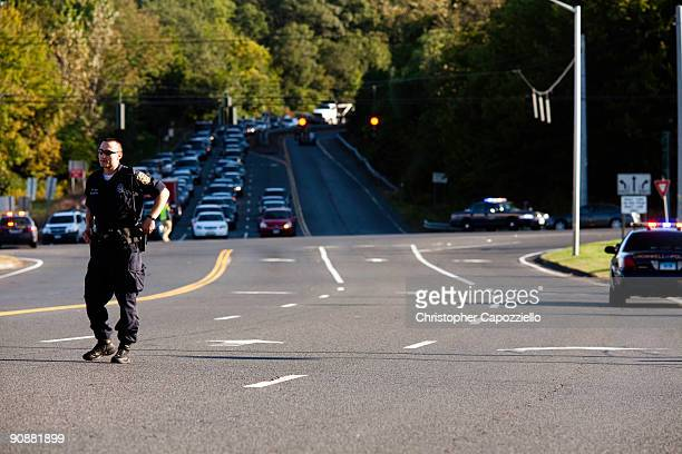 A police officer stands in the road as police cars move into the parking lot of a Super 8 Motel to make an arrest in connection with the murder of...