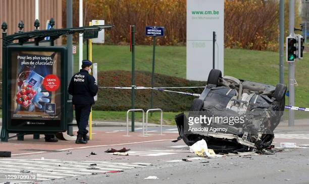 Police officer stands near a tumbled vehicle on Chaussee de Haecht road after an accident in Brussels, Belgium on November 21, 2020.