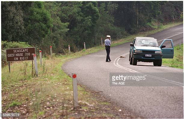 A police officer stands near a vehicle with bullet holes outside the Seascape Guesthouse after the Port Arthur massacre Tasmania 29 April 1996 THE...