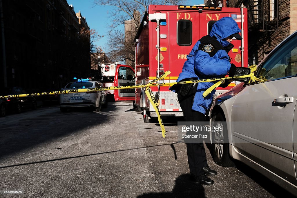 A police officer stands near the scene of a deadly in the Bronx on December 29, 2017 in New York City. At least 12 people, including at least four children were killed in the early evening blaze which officials believe was started by a child playing with the stove.