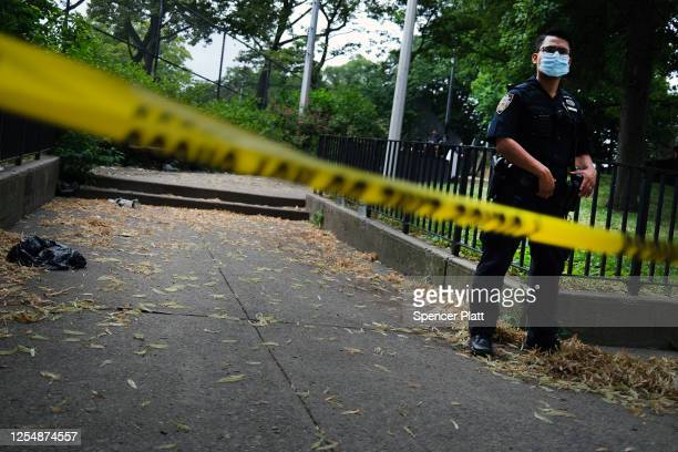 A police officer stands near the scene of an afternoon shooting that left one person dead on July 07 2020 in the Brooklyn borough of New York City...