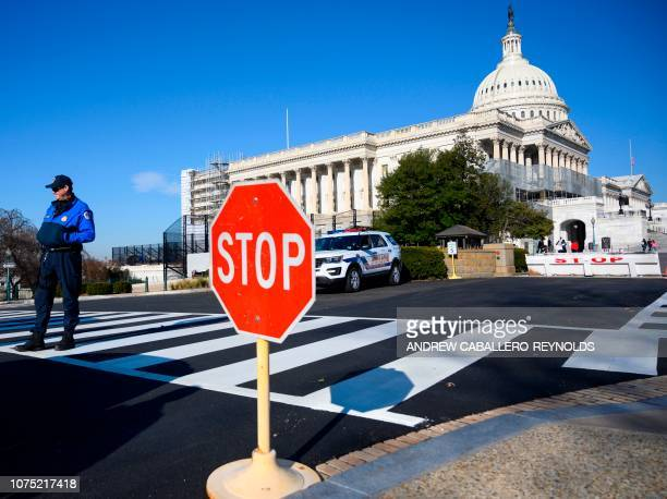 A police officer stands near the US Capitol during a government shutdown in Washington DC December 27 2018 Congress members trickled back into...