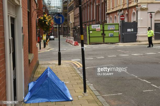 Police officer stands near to a small forensics tent as he mans a cordon at the junction of Church Street and Barwick Street, following a major...