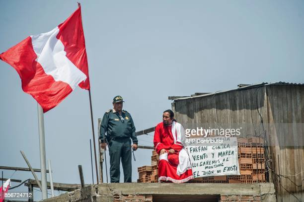 A police officer stands next to a football fan watching a training session of the Peruvian national team from the roof of a house in Lima on October...