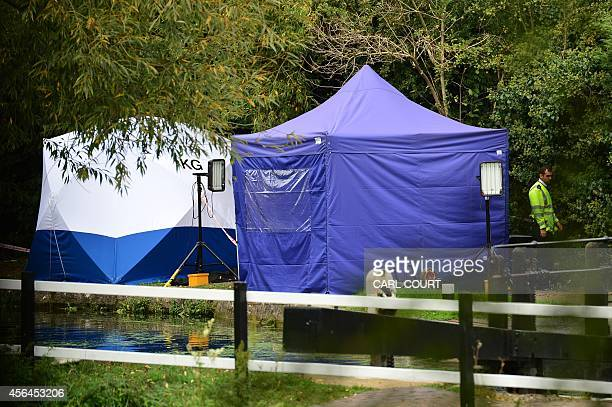 A police officer stands next to a forensics tent at the scene where a body was found during the search for missing schoolgirl Alice Gross in west...