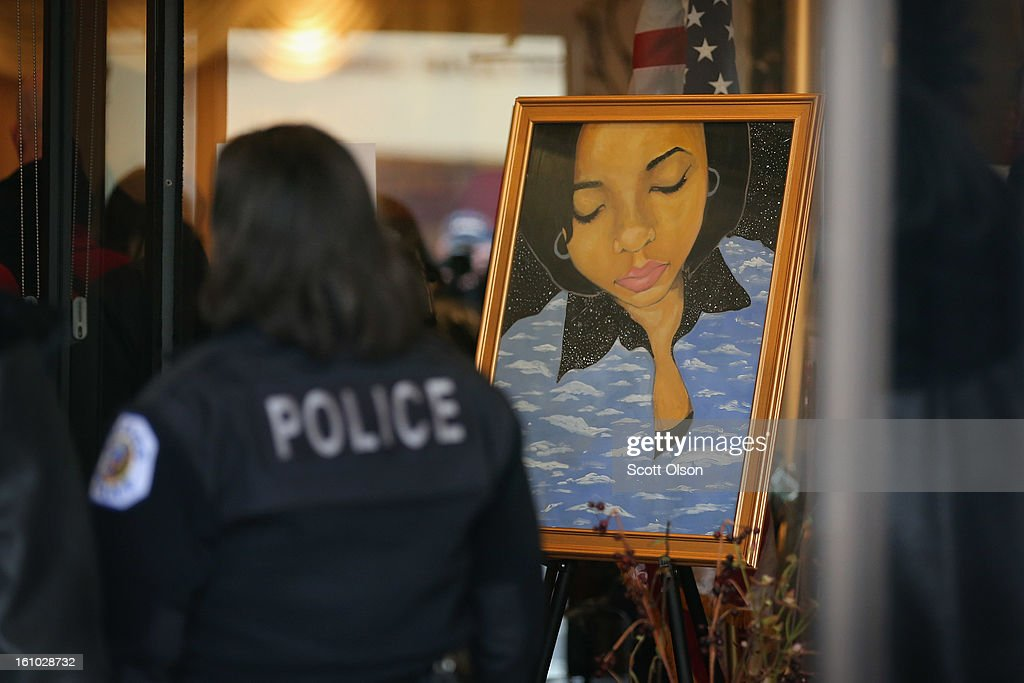 A police officer stands next to a painting 15-year-old Hadiya Pendleton, placed at the entrance of the Calahan Funeral Home during her wake on February 8, 2013, in Chicago, Illinois. Hadiya was killed when a gunman opened fire on her and some friends as they stood under a shelter on a warm rainy afternoon in a park about a mile from President Obama's Chicago home. First lady Michelle Obama is expected to attend tomorrow's funeral with senior White House adviser Valerie Jarrett and Education Secretary Arne Duncan.