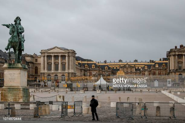A police officer stands next to a statue of French monarch Louis XIV in a front of the Chateau de Versailles in Versailles outside Paris during a...