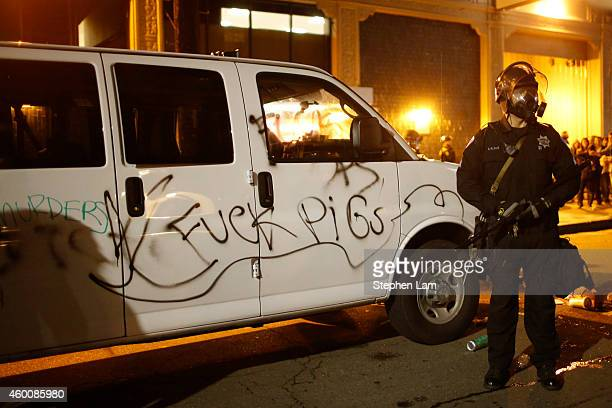 A police officer stands next to a vandalized police van during the fourth night of demonstrations over recent grand jury decisions in policeinvolved...