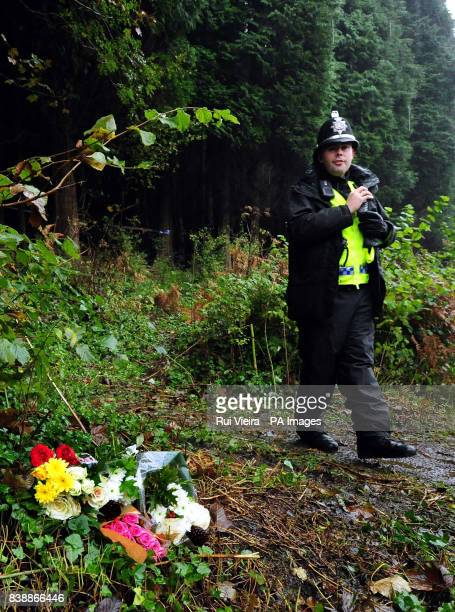 A police officer stands next to flowers outside woodland near the village of Aberkenfig Bridgend south Wales where the body of Rebecca Aylward was...