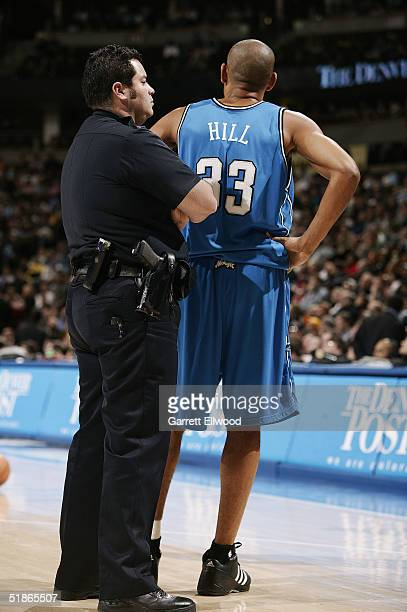 A police officer stands next to Grant Hill of the Orlando Magic during the game against the Denver Nuggets on December 6 2004 at Pepsi Center in...