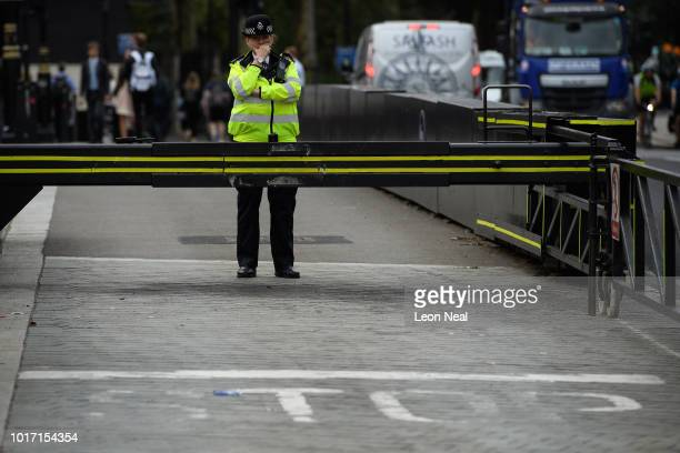 A police officer stands next to the barrier which stopped a speeding vehicle the previous day outside the Houses of Parliament on August 15 2018 in...