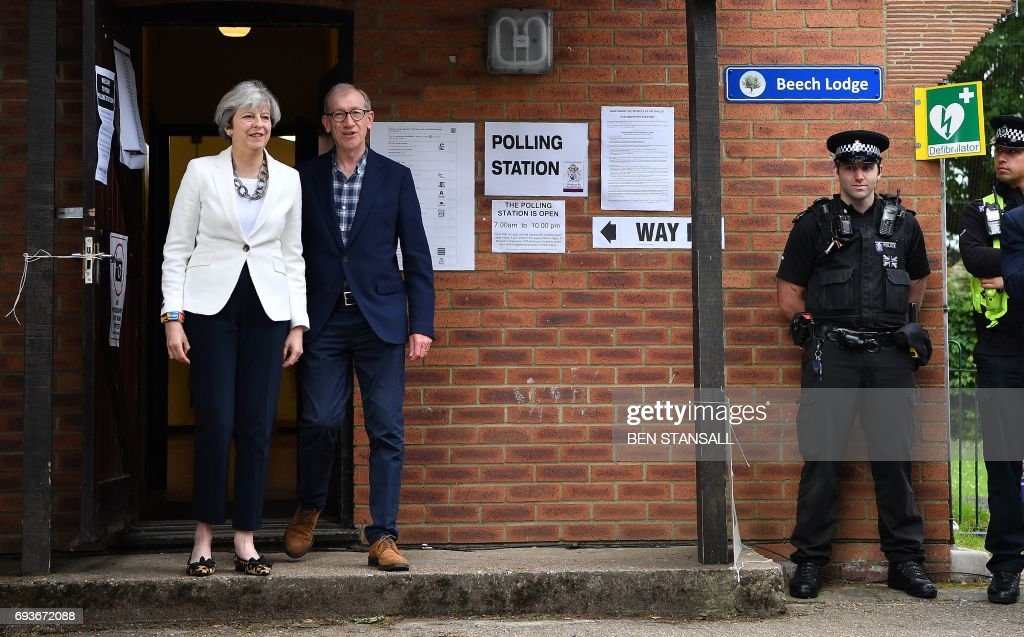 A police officer stands on duty as Britain's Prime Minister Theresa May and her husband Philip, leave a Polling Station after casting their ballot paper in Sonning, west of London, on June 8, 2017, as Britain holds a general election. As polling stations across Britain open on Thursday, opinion polls show the outcome of the general election could be a lot tighter than had been predicted when Prime Minister Theresa May announced the vote six weeks ago. / AFP PHOTO / Ben STANSALL