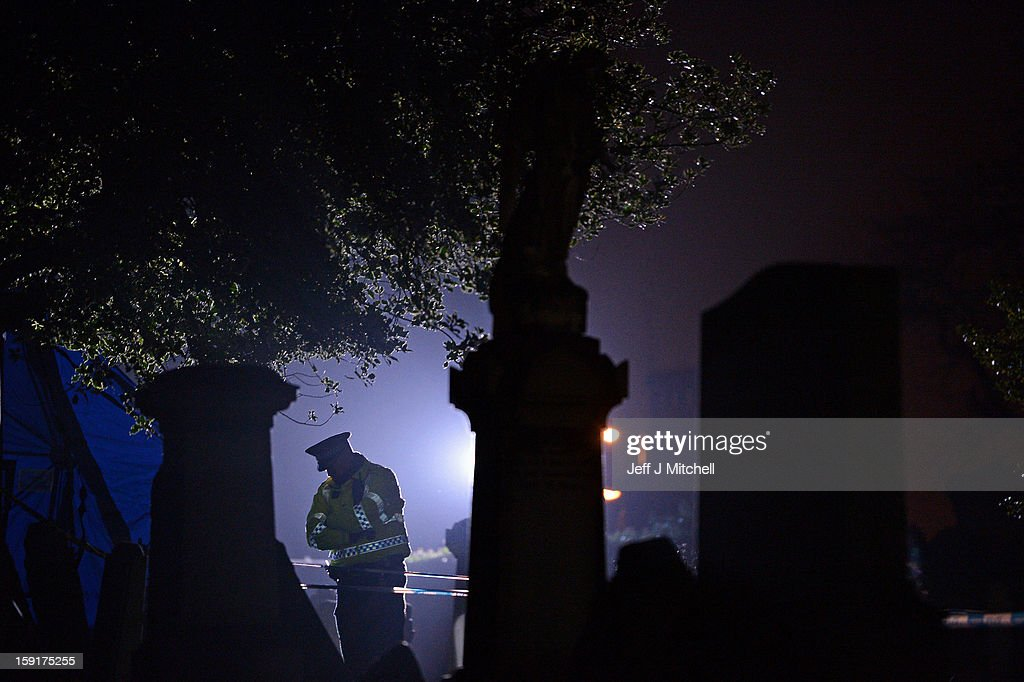 A police officer stands on duty at Monkland Cemetery as forensic officers continue to exame a burial plot on January 9, 2013 in Coatbridge, Scotland. Forensic specialists are exhuming remains at a gravesite in search of 11 year old school girl Moira Anderson, who went missing in 1957.