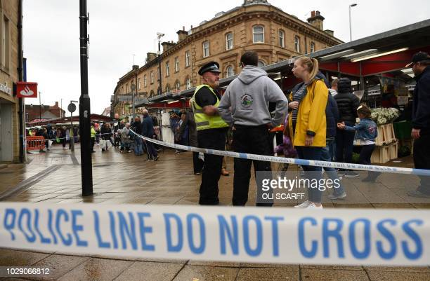 Police officer stands on duty by a police cordon in Peel Square, following a stabbing incident in the centre of Barnsley, northern England on...