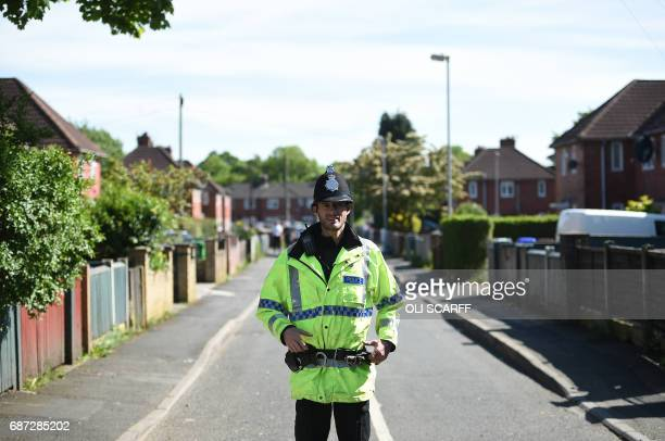 A police officer stands on duty on a cordonedoff road in Fallowfield Manchester in northwest England on May 23 as they search a nearby resdiential...
