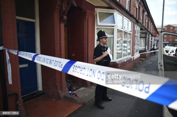 A Police officer stands on duty outside a residential property on Banff Road in Rusholme Manchester northern England on May 31 as police...