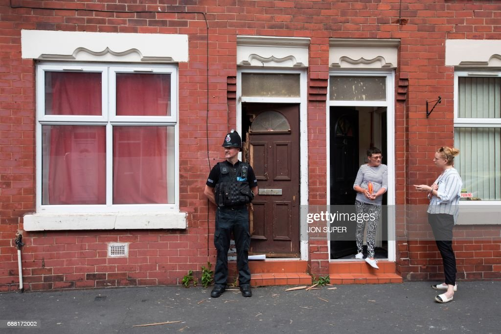 A police officer stands on duty outside a residential property on Lindum Street in Moss Side, Manchester, on May 25, 2017, as their investigations continue into the May 22 terror attack at the Manchester Arena. Britain Thursday closed in on a jihadist network thought to be behind the May 22, 2017 Ariana Grande concert attack, as grief mixed with anger at the US over leaked material from the probe. Britain has raised its terror alert to the maximum level and ordered troops to protect strategic sites after 22 people were killed in a suicide bomb attack on a Manchester pop concert. /