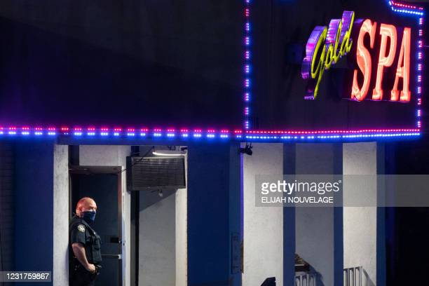 Police officer stands outside a massage parlor where three people were shot and killed on March 16 in Atlanta, Georgia. - Eight people were killed in...
