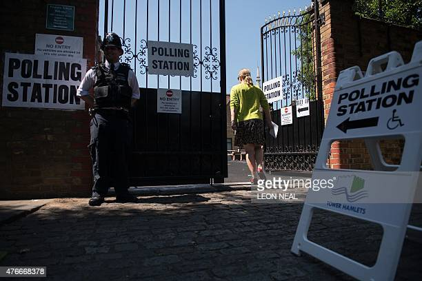 A police officer stands outside a polling station in the Tower Hamlets borough of London on June 11 2015 as local elections take place Voters went to...