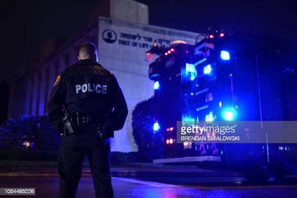A police officer stands under the rain outside the Tree of Life Synagogue after a shooting there left 11 people dead in the Squirrel Hill...