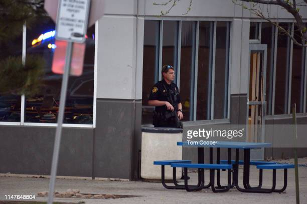 A police officer stands watch at the scene of a shooting in which at least seven students were injured at the STEM School Highlands Ranch on May 7...