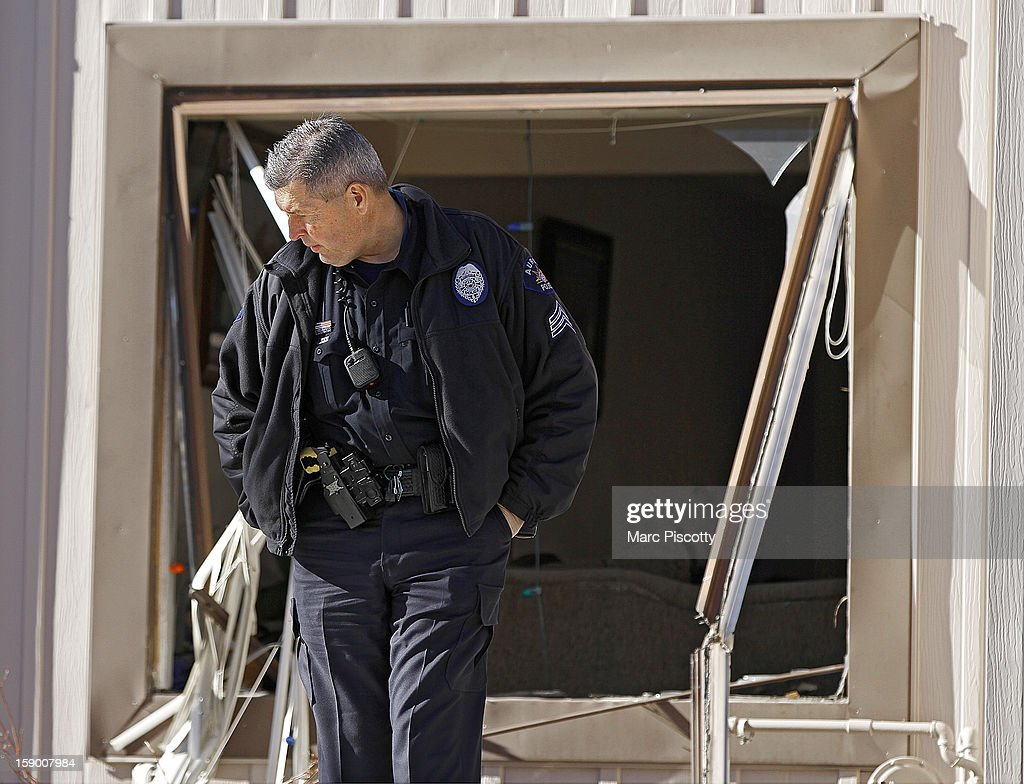 A police officer stands watch in front of a broken out window in a town home where four people were killed Saturday morning including the gunman who held police at bay for several hours at the complex January 5, 2013 in Aurora, Colorado. Aurora SWAT team members shot a gunman after he went to a second-floor window and fired at police. The gunman also allegedly fatally shot two men and a woman that he had taken hostage. One woman managed to escape from an upstairs back window, ran from the home and called police just before 3 a.m., said Cassidee Carlson, Aurora police spokeswoman.