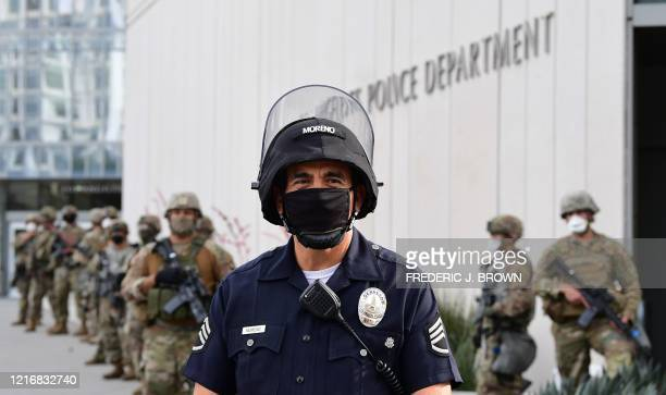 Police officer stands with armed members of the National Guard facing protesters marching over the death of George Floyd, an unarmed black man, who...