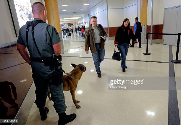 A police officer stands with his dog Rex in front of the security checkin gates at HartsfieldJackson International Airport in Atlanta Georgia US on...