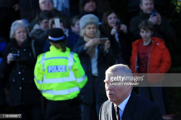 A police officer stands with wellwishers as Britain's Prince Andrew Duke of York arrives to attend a church service at St Mary the Virgin Church in...