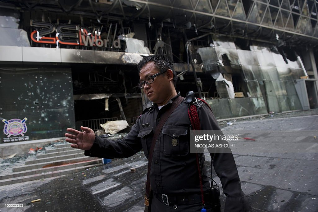 A police officer stops the media from getting close to the site of a fire at Thailand's biggest shopping mall - Central World - after it was set ablaze the day before following an army assault on an anti-government protest site in downtown Bangkok on May 20, 2010. Thailand's biggest shopping mall faces collapse after it was set ablaze by enraged protesters in the wake of an army offensive to shut down an anti-government rally, police said. AFP PHOTO/ Nicolas ASFOURI