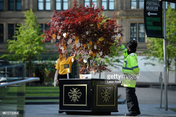A police officer stops to read some of the handwritten messages left on one of the 'Trees of Hope placed throughout the city on the morning of the...