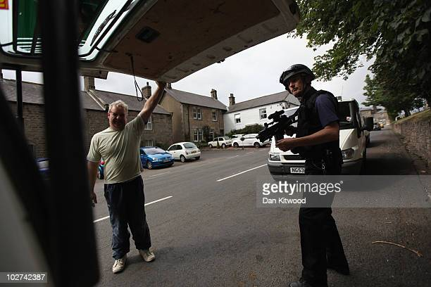 Police officer stops traffic as part of the ongoing search for Raoul Moat on July 9, 2010 in Rothbury, England. Police continue to search the village...
