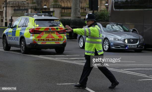 A police officer stops traffic as the Jaguar car of British Prime Minister Theresa May is driven away from the Houses of Parliament in central London...