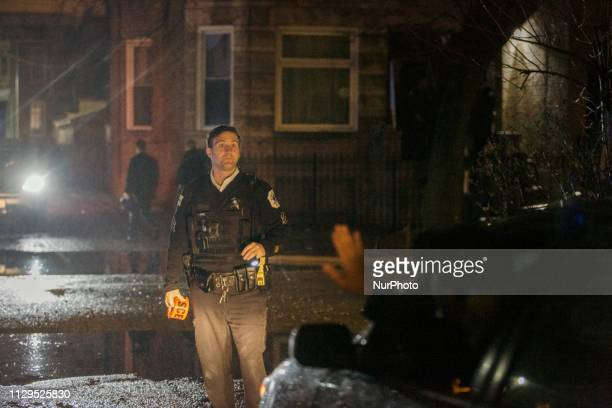 Police officer stops traffic in an alleyway in front of the crime scene in a apartment raid in Humboldt Park In Chicago, Illinois, on 10 March 2019....