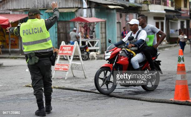 A police officer stops two men on a motorbike druing a patrol in Tumaco a municipality in the Colombian department of Narino near the border with...