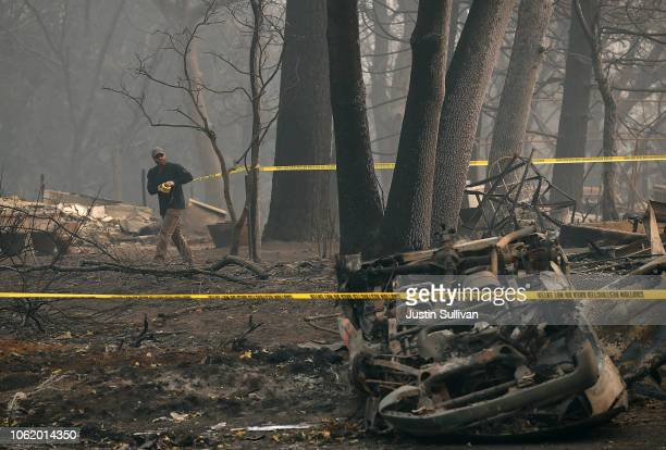 A police officer stretches crime scene tape around an area where human remains were found in a car that was destroyed by the Camp Fire on November 15...
