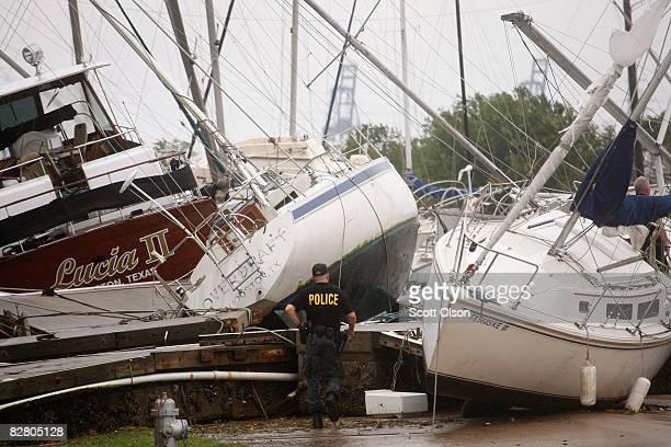 A police officer surveys damage to boats after the dock they were tied to broke free during Hurricane Ike and washed them into a parking lot...