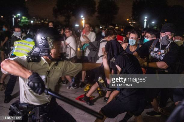Police officer swings his baton as he restrains a protester during the clear up after the clash outside the Legislative Council in Hong Kong after a...
