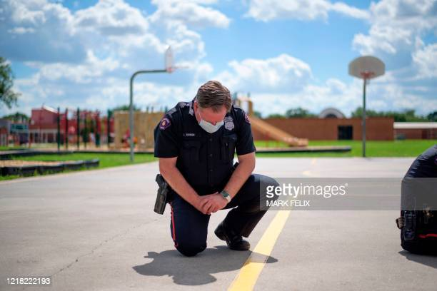 TOPSHOT A police officer takes a knee during a 9 minute moment of silence in honor of George Floyd during a Sit In Protest to mourn the death of...
