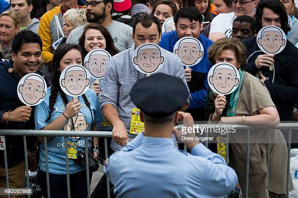 """Police officer takes a photo of a group holding """"Pope Emoji"""" smasks while they wait for Pope Francis to arrive at Cathedral Basilica of Saints Peter..."""