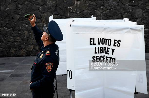 TOPSHOT A police officer takes a selfie during general elections in Mexico City on July 1 2018 Sick of endemic corruption and horrific violence...