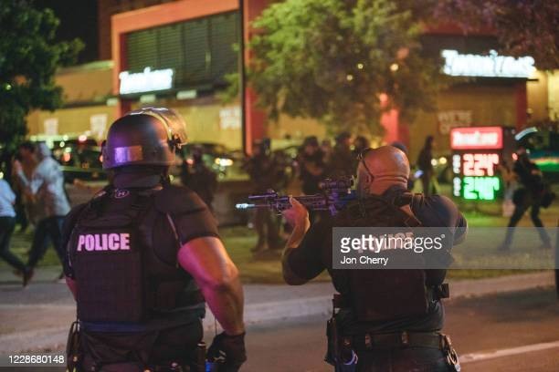Police officer takes aim at protesters shortly after shots are fired at police, resulting in two injured officers, on September 23, 2020 in...
