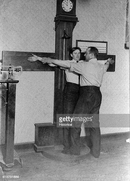 A police officer takes Bertillon measurements of a suspect's[] arm span at New York Police Headquarters The Bertillon system is a series of physical...