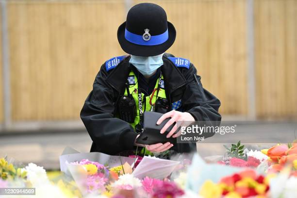Police officer takes photos of floral tributes laid near the former home of Captain Sir Tom Moore following the announcement of his death the...
