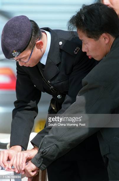 A police officer takes the fingerprints of one of the 156 illegal immigrants 121 men and 35 women aged between 18 and 51 are arrested in the holding...