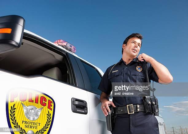 Police Officer Talking on Radio by Patrol Vehicle