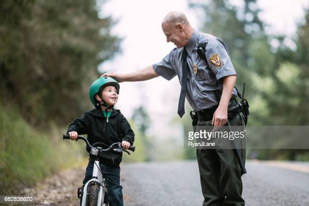 police officer talking to child on bike - cycling helmet stock pictures, royalty-free photos & images